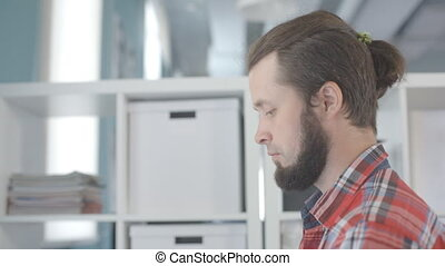 A man with a beard and a tuft of hair on head, works in office.