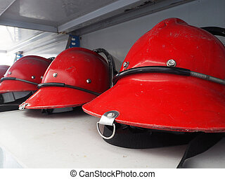 Red fireman helmet prepared on shelf.