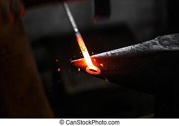 Anvil in smithy - The blacksmith manually forging the molten...