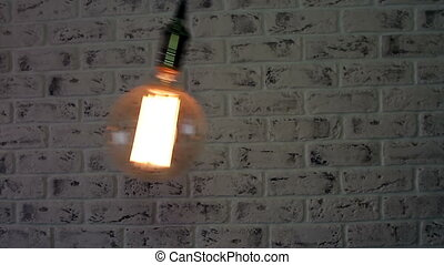 Vintage Loft lamp swinging on a brick wall background