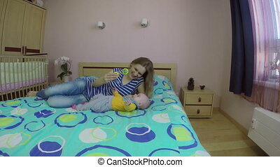 mom play with baby girl on bed. Happy motherhood concept. 4K...