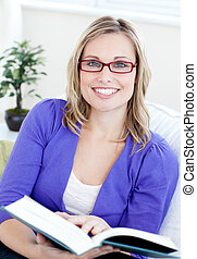 Portrait of an attractive woman with glasses reading a book