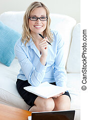 Confident businesswoman holding a pen wearing glasses...