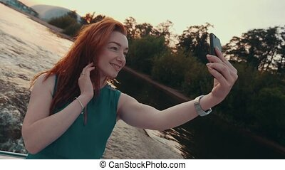 Young red hair girl in turquoise dress take selfie on...