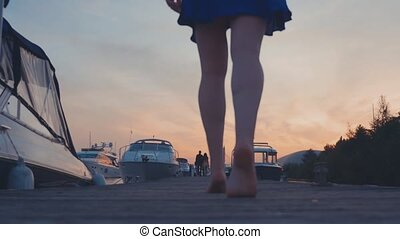 Young girl in blue dress walk on wooden pier at coast on sunset. White yachts
