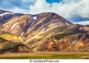 Multi-color picturesque rhyolitic mountains are lit with the...