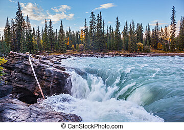 Scenic and powerful Athabasca Falls. Sunset illuminates the...