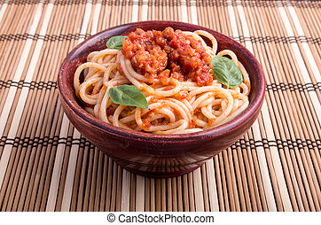 Italian spaghetti with tomato relish and basil leaves in a...