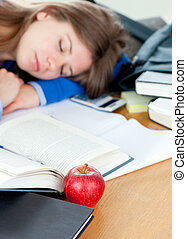 Young woman sleeping on a desk after doing homework