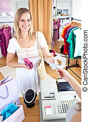 Caucasian woman is paying items in a clothes shop