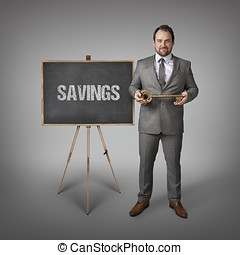 Savings text on  blackboard with businessman and key
