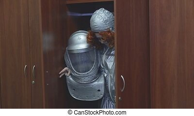 Robot woman with red curly hair in grey space suit, glasses...