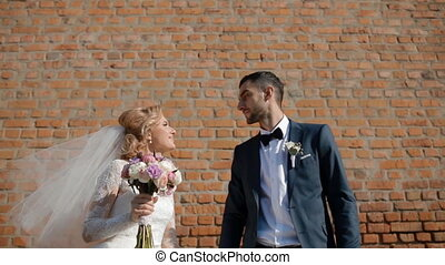 Bride and groom kiss in front of of the brick wall.