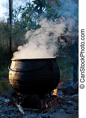 black pot - black cast iron pot boiling on a fire with steam...