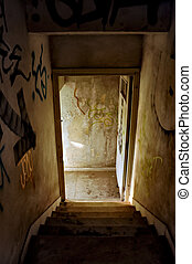 abandoned house staircase - Staircase and exit door of an...