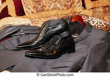 Shiny black men's shoes for the bride, lying on the floor...