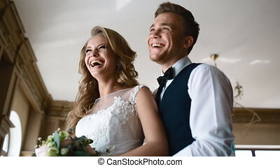 Bride and groom laugh near the window
