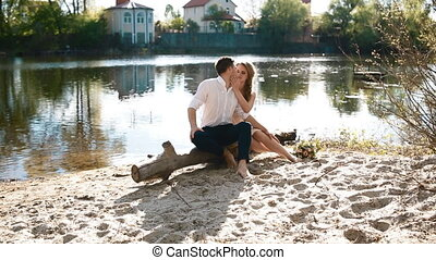 Young couple pose outdoor near the river sitting on the...