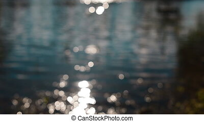Reflection of sunlight on the river water. Blurred...