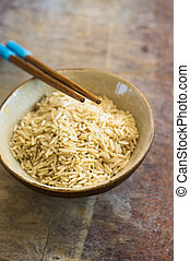 wild rice in ceramic bowl and chopsticks on wooden...