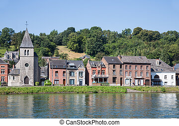 Houses and little church along Meuse river in Dinant,...