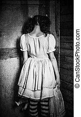 Strange girl stands turned to wall. Rear view. Grunge...