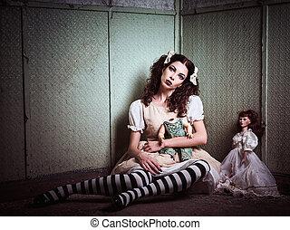 Strange sad girl with dolls sitting in forsaken place -...