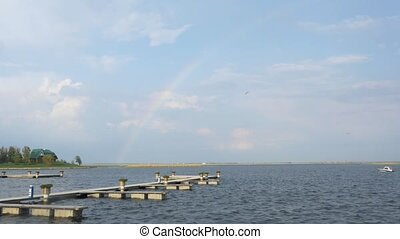 Rainbow over the river and sailing boat