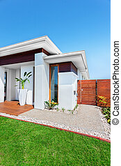 Modern house with a lawn on clear blue sky - The lawn has...