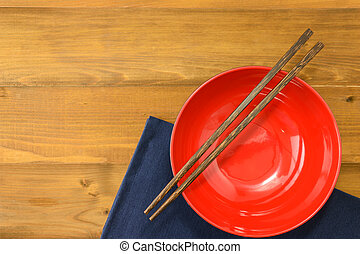 red empty bowl with chopsticks on wooden table and dark blue...