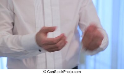 Man wears cufflinks on the cuffs of his shirt. Close up -...