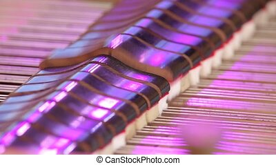 Hammers striking strings inside the piano. Close up
