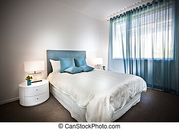 Modern bed with white sheets and blue pillows with table...