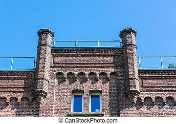 Old brick house against blue sky.