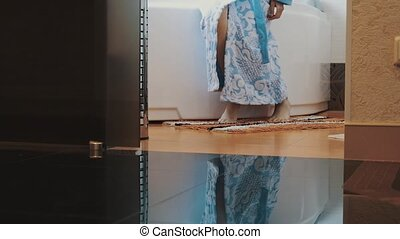 Girl in blue bathrobe stand up from white bath walk out of...