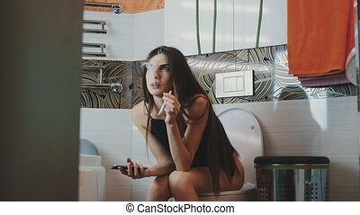 Girl sitting on toilet holding phone. Smoking electronic...