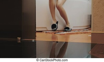 View of young woman in slippers stand up from bath and walk...