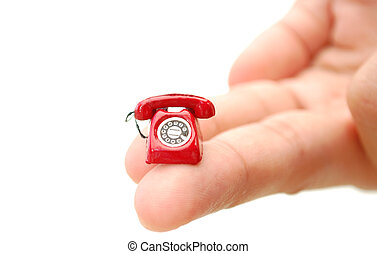 Telephone - Miniature red telephone held by fingers of a...