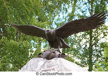 bronze eagle taking off a stone monument - A bronze eagle...