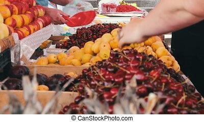 Showcase Fruits. Woman chooses fruits on spontaneous market...