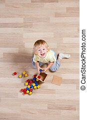 top view of happy kid playing with colorful toys on floor
