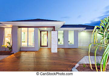 Front of the lights turned on modern mansion with wooden...