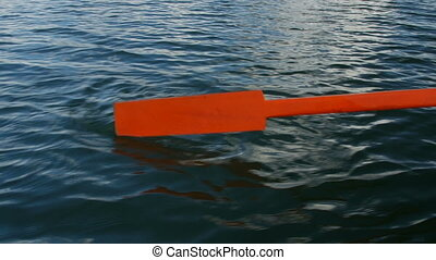 Old wooden paddle bounces into lake water - Old wooden...
