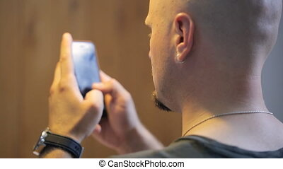 Bald person with beard types text messages on smartphone. He...