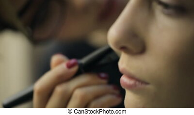 Close up view of woman model getting make up.