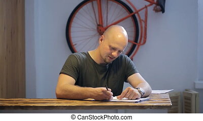 Bald bearded man sits at wooden table in studio.