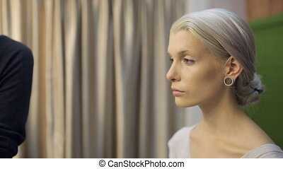 Close up view of female model making up. Young woman is...