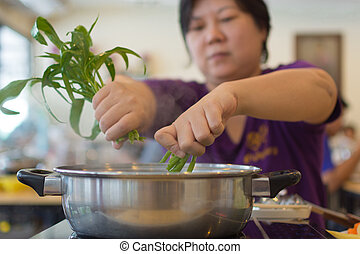 Asia woman cooking by put a vegetable in to a hot pot - Asia...