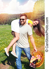 Happy couple having fun on nature - Smiling man holding...