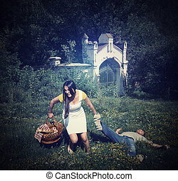 Woman pulling a slapped man after a picnic on nature